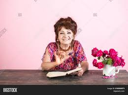 pension and retirement old age old woman reading book with gles at flowers happy