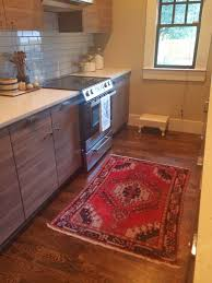 in vogue red rubber kitchen rugs on brown wooden floors as well as white acrylic countertop and brown hardwood kitchen cabinets in small kitchen ideas
