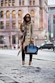 maria vizuete wears a classic beige trench coat with white stis and an oversized scarf to
