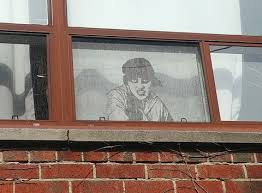 realistic window drawing. black and white realistic drawing of a sneering woman with hat on looking out window