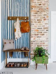 a natural nook in the wall is transformed into the perfect entryway catchall with hooks for hanging items like coats and bags a bench and shoe tray make it