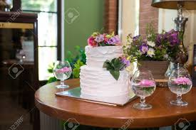 White 2 Tiered Wedding Cake Decorated With Pink And Lilac Flowers