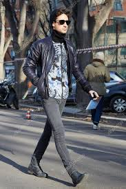 elegant man with blue leather jacket poses for photographers before emporio armani fashion show stock