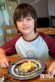a 12 year old boy eating breakfast