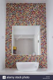 bathroom wash basin with colorful glass mosaic tileirror inset into the tiles