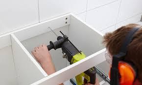 installing bathroom vanity. man installing bathroom vanity to wall