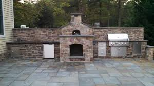 custom stonework outdoor kitchen with fireplace