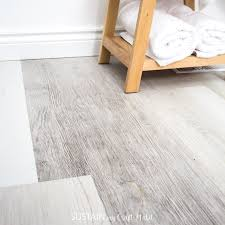 grey distressed luxury vinyl plank flooring in a small bathroom