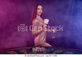 Girl playing poker at casino, holding glass of champagne, two aces. posing  at table with chips, money on it. black, smoke | CanStock