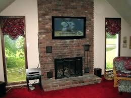 mounting a tv above fireplace black brown brick between two tall glass window with stone abo mounting a tv above fireplace