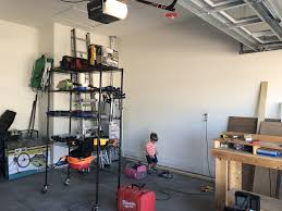 this is my tool side of the garage that black rolling rack is usually against the wall where aiden is standing and then my rolling table saw stand and huge