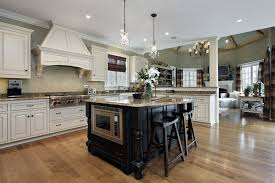 kitchen with white cabinets and black cabinet with beige granite custom island