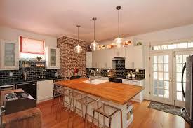 rustic kitchen with brick fireplace and black tile backsplash