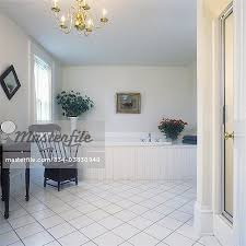 white ceramic tile floor. BATHROOMS - Country White, Large Bathroom, View Towards Wood Framed Whirl Pool Tub, White Ceramic Tile Floor, Shower Stall To Far Right, Antique Potty Floor L