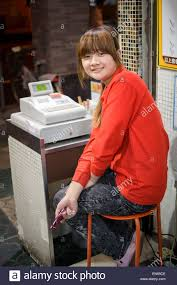 Young Cheerful Chinese Woman Working As A Cashier At A Cash
