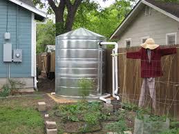galvanized metal cistern by garage rainwater collection for urban gardening