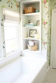 chic kids bathroom features a wainscoted tub under windows flanked by built in shelving