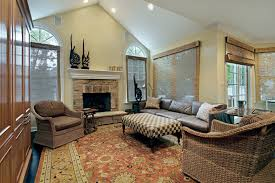 This eclectic living room features a small stone fireplace, wicker chairs  paired with a leather