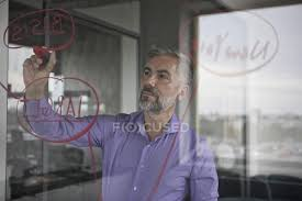 businessman writing on glass wall in office stock photo