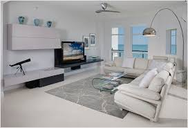living room contemporary arco lamp area rug gray greige hearth lucite lucite coffee table minimal modern fireplace ocean view sectional sofa telescope vase