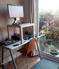 an end table placed on a normal height desk makes a makeshift standing desk