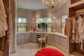 gray walk in closet features gray built ins fitted with a makeup vanity and a white cane back chair placed under a window dressed in cafe curtains