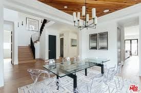 the dining room boasts glass dining table and glass chairs along with candle chandelier and a