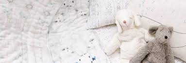 a lamb blush and mouse play lie atop white and blue quilts and sheets in a