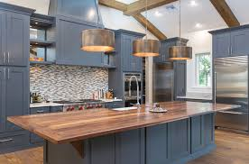 contemporary kitchen with bronzed drum pendant lights above wood countertop island