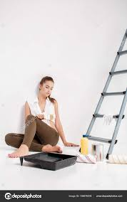 woman painting a wall in house stock photo
