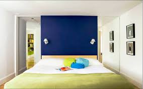 simple bedroom with a large block of blue behind the headboard