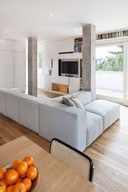 amazing home living room interior designed with light grey sectional sofa completed with ceiling height bookcase beautiful living room pillar