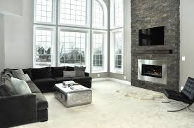 living room black fabric sofa on white rug added by grey stone fireplace and glass