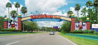 an entrance of walt disney world resort some cars are visible