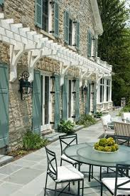 teal shutters traditional exterior and french doors glass top round table iron fence lanterns outdoor dining