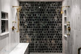 elegant walk in shower is located behind a seamless glass enclosure and fitted with glossy black grid floor tiles and a black and gold beehive tiled accent