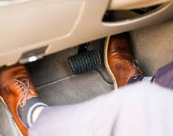 businessman s feet in wheel well pressing gas and brake pedal
