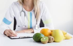 an image shows an ortment of fruit in the foreground with a doctor writing on a