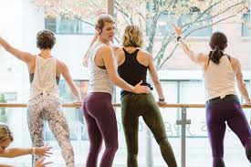 a barre3 teacher guiding a student in an exercise