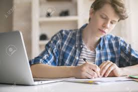 close up of casual young man writing essay at desk blurry  close up of casual young man writing essay at desk blurry laptop white brick