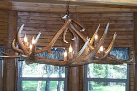 4 antler dining room table light made from 2 very large elk antlers along the bottom with 2 more large elk antlers holding it to the chain