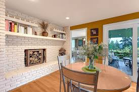 modern dining room with maple natural solid hardwood plank custom floating shelves painted brick