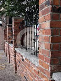 Brick and wrought iron fence decorated with arrowheads on top