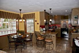 pendant lights above small marble countertop kitchen island and round wooden dining table also four