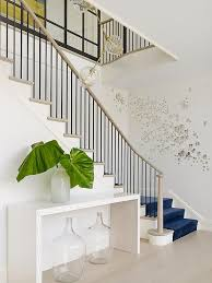 eclectic foyer features a light taupe staircase lined with a royal blue velvet stair runner as well as butterfly wall art alongside a pair of wine jugs  on stairway wall art with eclectic foyer features a light taupe staircase lined with a royal
