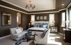 brown walls black furniture. master bedroom layout with sitting area and brown walls white border trims chandelier black furniture