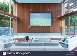 design stunning living room. Interior Design Woman Watching Large Flat Screen Tv In Modern Living Room Dc3jer Stock Stunning Sitting I