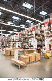 stock photo blurred customers shopping in large furniture warehouse with row of aisles and bins from floor to
