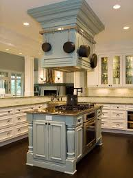 In this transitional kitchen, a pale blue island houses the oven, gas  cooktop and mounted range hood. Equipped with a pot rack, pot filler and  extra ...