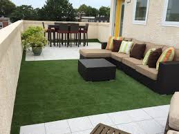 the outdoor modular grass tile is an easy to install snap outdoor flooring over grass